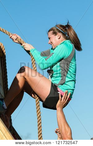 BUFORD, GA - NOVEMBER 2015:  A woman struggles to use a rope to climb up a wall at one of the obstacles at the Muddy Brute Challenge in Buford, GA on November 21, 2015.