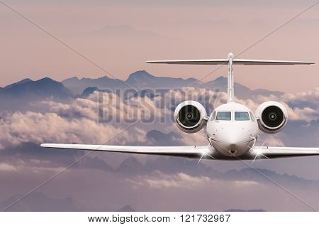 Private Jet plane over clouds and Alps mountain on sunset. Front view of a big passenger or cargo ai