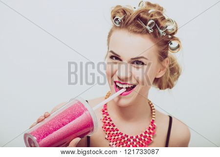 Happy, young woman drinking, using a straw. Curlers on her hair.