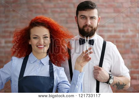 Two professional hairdressers on brick wall background