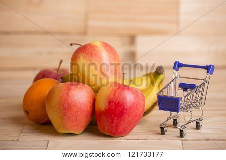fruits and a shopping cart on a wooden table, studio picture