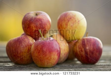Ripe red apples on a wooden table, on green outdoor background