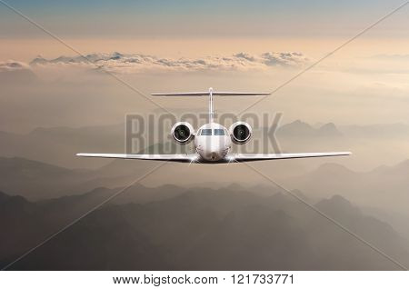 Airplane fly over clouds and Alps mountain on sunset. Front view of a big passenger or cargo aircraf