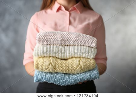 Stack of knitted clothes in female hands on grey blurred background