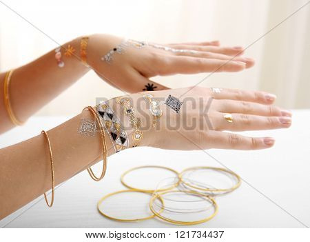 Silver, golden flash tattoo and bracelets on female hands over white background