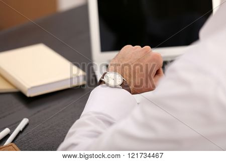 Businessman checking the time on his wrist watch, close up