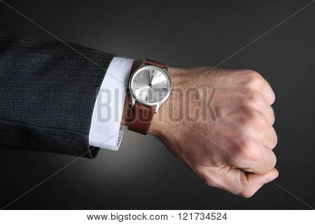 Modern watch on a businessman's wrist over black background