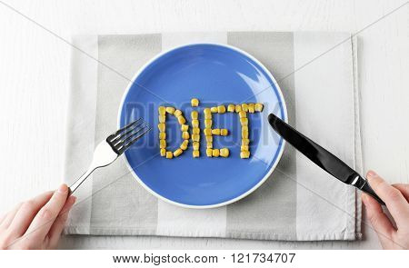 Female hands holding knife and fork on plate with word DIET of corn, top view