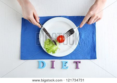 Female hands holding knife and fork on plate with cherry tomato and lettuce leaf near, top view