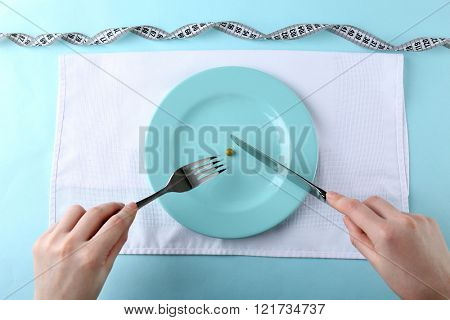 Female hands holding knife and fork on plate with single pea, top view
