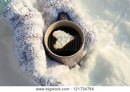 Female hands in warm mittens holding cup of hot coffee with heart marshmallow on snowy background