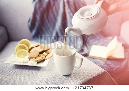 Woman pouring tea in mug from kettle