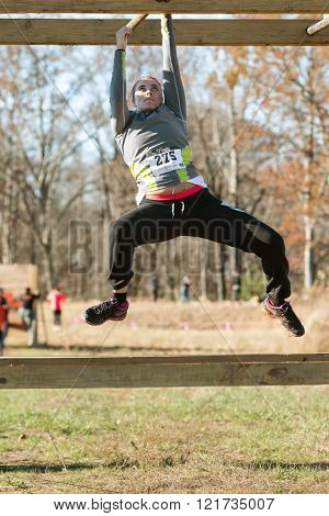 BUFORD, GA - NOVEMBER 21:  A young woman grips a metal bar as she tries to pull herself across an obstacle while suspended over the ground, at the Muddy Brute Challenge in Buford, GA on November 21, 2015.