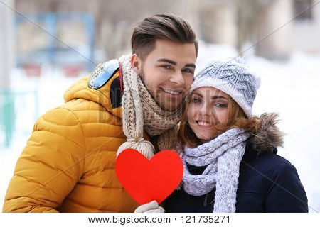 Young couple in love holding red paper heart outdoors in winter