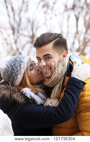 Young woman kissing her boyfriend outdoors in winter