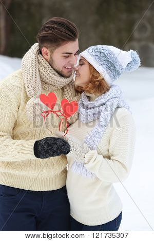 Young couple in love holding red paper hearts outdoors in winter