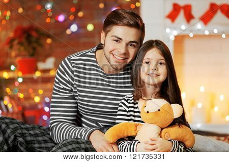 Older brother with little sister sitting in Christmas living room