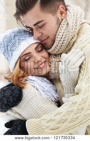 Young couple embracing outdoors in winter, close up