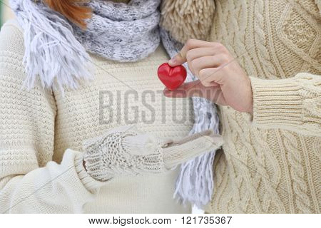 Young couple in love holding small red heart outdoors in winter