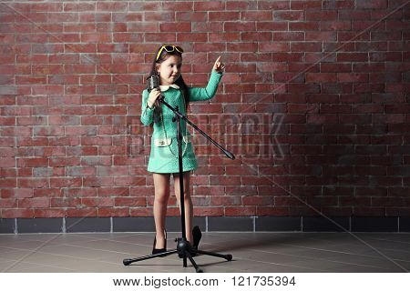 "Beautiful little girl in dress and ""MOTHER'S HEELS"" with microphone on brick wall background"