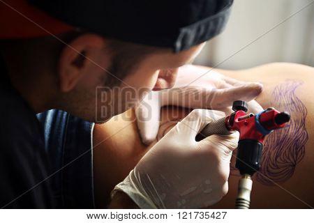 Tattooist makes tattoo, close up