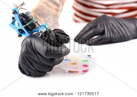 Tattoo master working in black medical gloves with tattoo machine, close up