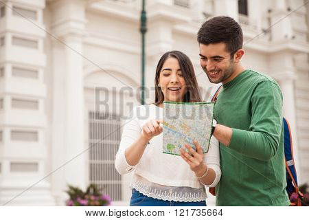 Cute Hispanic Couple Reading A Map