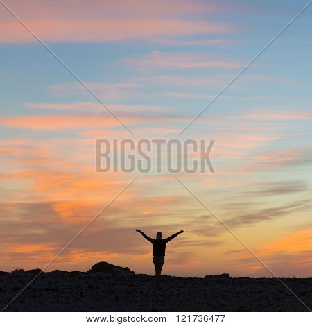 Woman enjoying freedom at sunset.