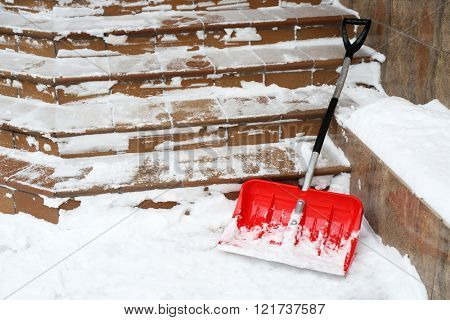 Red shovel for snow removal beside stairs