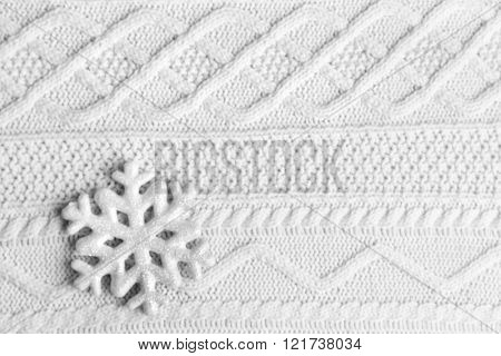 Winter background blur with snowflake on knitted background