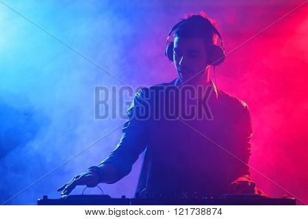 DJ playing music at mixer on colorful foggy background