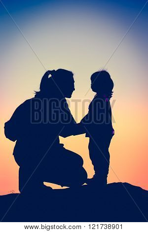 Silhouette side view of mother and child hikers enjoying the view at the top of a mountain. Cross pr