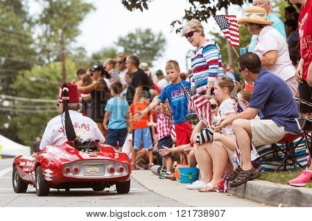 ALPHARETTA, GA - AUGUST 2015: Families sit on curb with American flags and interact with participants along the parade route of the Old Soldiers Day Parade in Alpharetta GA on August 1 2015.