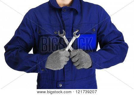 A repairman with crossed arms holding wrenches, on white background, close-up