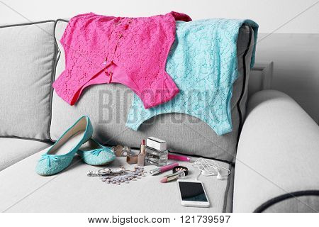 Composition of woman's fashion look on a gray couch