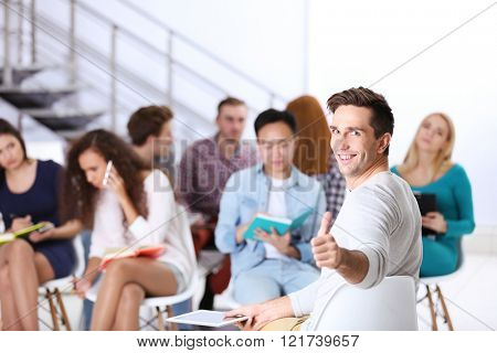 Happy young man sitting in front of people at the office meeting