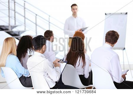 Young businessman making a presentation on a board in the office