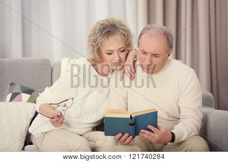 Happy mature couple reading book together on a sofa at home
