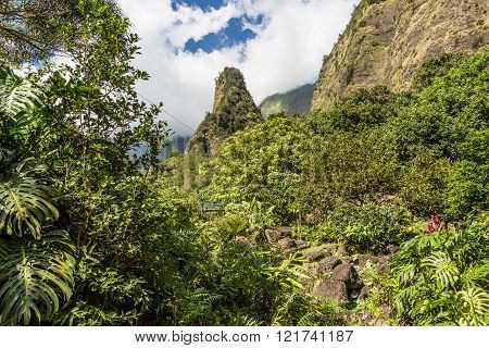 Iao Needle State Park in Central Maui. The Iao Needle is a solid green needle-like mountain shooting straight up to the sky. Iao Valley State Park is located in Central Maui near Wailuku