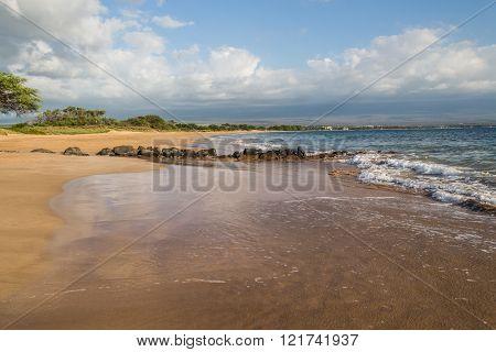Beautiful gold sand and crystaline blue waters in the Kealia Beach Maui near the Kealia National Wildlife Refuge