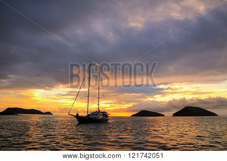 Silhouetted Tourist Sailboat At Sunrise Anchored Near Chinese Hat Island, Galapagos National Park, E