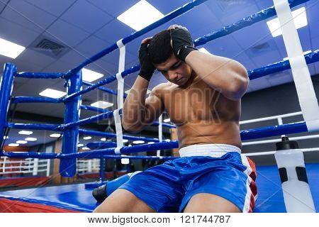 Handsome male boxer resting in gym