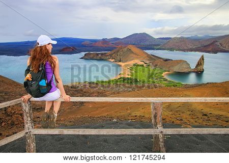 Young woman enjoying the view of Pinnacle Rock on Bartolome island Galapagos National Park Ecuador. This island offers some of the most beautiful landscapes in the archipelago.