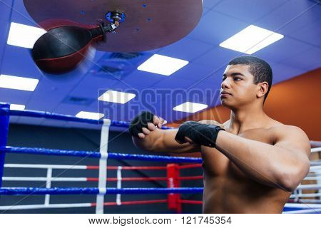 Handsome boxer exercising with the speed bag