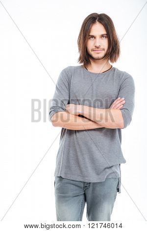 Attractive serious young man with long hair standing with arms crossed over white background