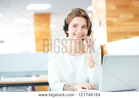 Cheerful attractive young woman sitting and working in call center with headset and laptop in office