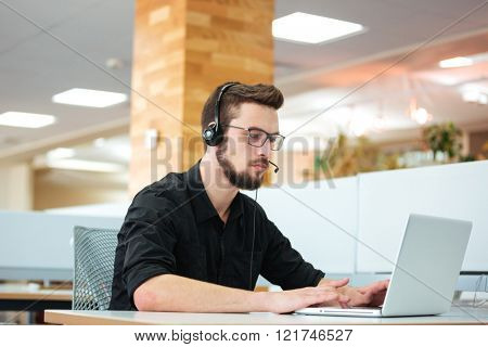 Businessman working on laptop computer in call center