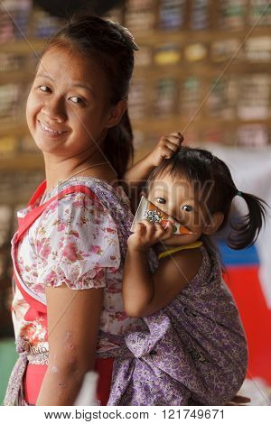 PHANG MAPHA, THAILAND, NOVEMBER 19, 2012 : A mother from a Karen tribe is carrying her daughter on her back, wrapped in a cloth, phang Mapha (Soppong), Thailand