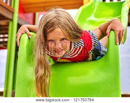 Child girl upside down on  park playground game. Girl slides on children's slide.