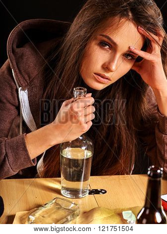Drunk girl keeps bottle of alcohol. Soccial issue alcoholism. Alcoholic woman.